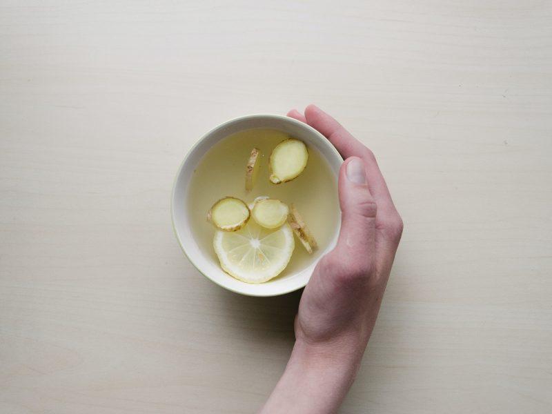 Das Bild zeigt eine Tasse Tee von oben. Eine Hand greift die Tasse von rechts.