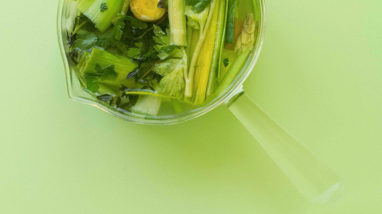 Bild zeigt einen Topf mit Gemüsebrühe in einem grünen Farbspektrum