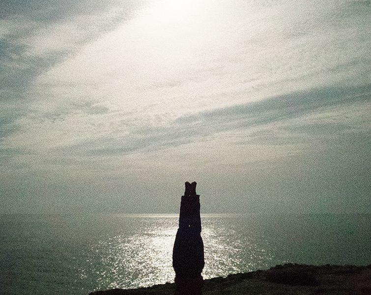 Bild zeigt einen Stein auf einer Klippe vor dem Ozean.Der Himmels ist mit Schleierwolken durchzogen und die Sonne spiegelt sich am Wasser.