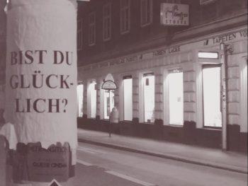 """Das Bild zeigt einen Laternenpfahl.Auf dem ist ein Plakat geklebt mit der Aufschrift: """"Bist du glücklich?"""""""