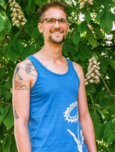 Das Bild zeigt mich im Portrait vor einem Kastanienbaum. Ich trage ein blauen Trägershirt mit einer weißen Blume.