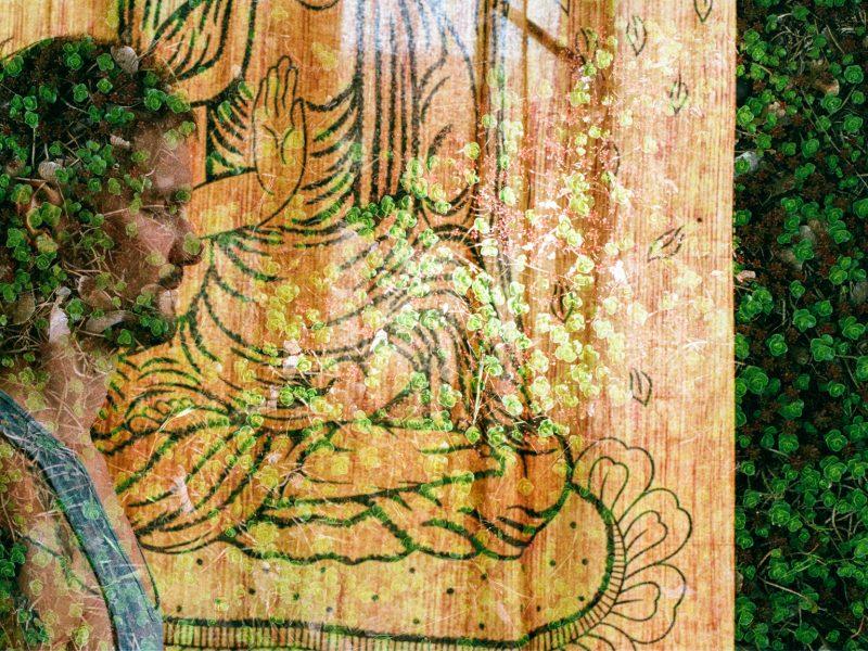 Das Bild ist ein double exposure Bild und zeigt mich beim meditieren vor einem orangenem Vorhang mit einem Buddha