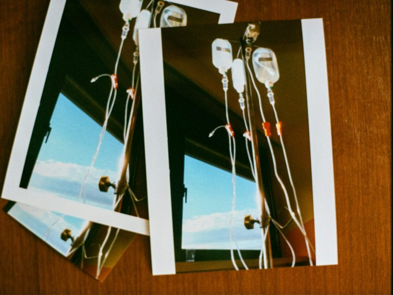 Das Bild zeigt ein Photo von Chemotherapie-flaschen vor einem Fenster durch das der blaue Himmel sichtbar ist.