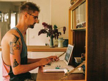Das Bild zeigt mich beim Schreiben vor dem Laptop auf meinem Arbeitsplatz. Im Hintergrund steht eine Vase mit Flieder