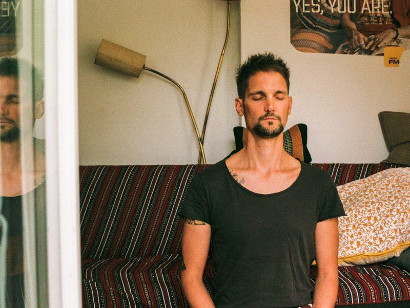 Beim Bild bin ich beim mediteren zu sehen. Ich trage ein schwarzes Shirt und im Hintergrund ist eine Coach mit roter Decke