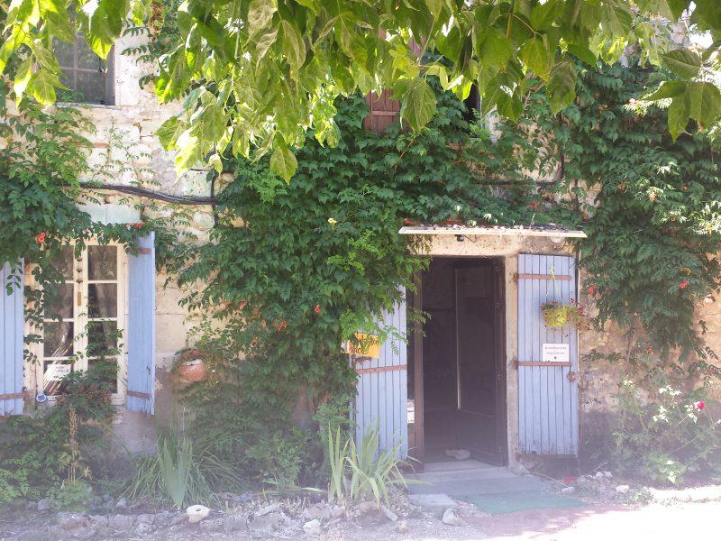 Zu sehen ist ein Steinhaus mit geöffneter Tür