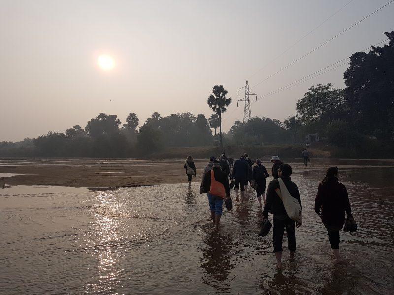Das Bild zeigt Menschen, die bei Sonnenuntergang durch einen Fluss gehen. Der Himmel ist staubig und das Licht bricht sich golden im Wasser.