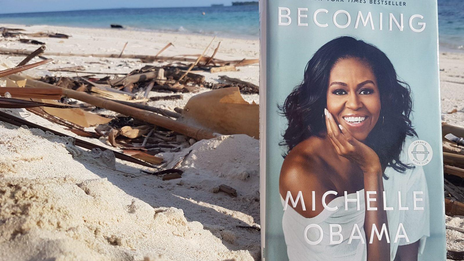 """Das Bild zeigt das Buch """"Becoming"""",von Michelle Obama auf einem Sandstrand positioniert"""