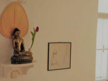 Bild zeigt eine Buddhastatue,die auf einem kleinen Holzregal steht. Daneben ist eine kleine Zeichnung und ein Holzkastenfesnter zu sehen