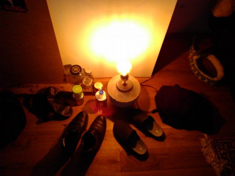 Das Bild zeigt eine Lampe am Boden. Sie strahlt warmes Licht aus. Neben der Lampe stehen mehrere Paar Schuhe