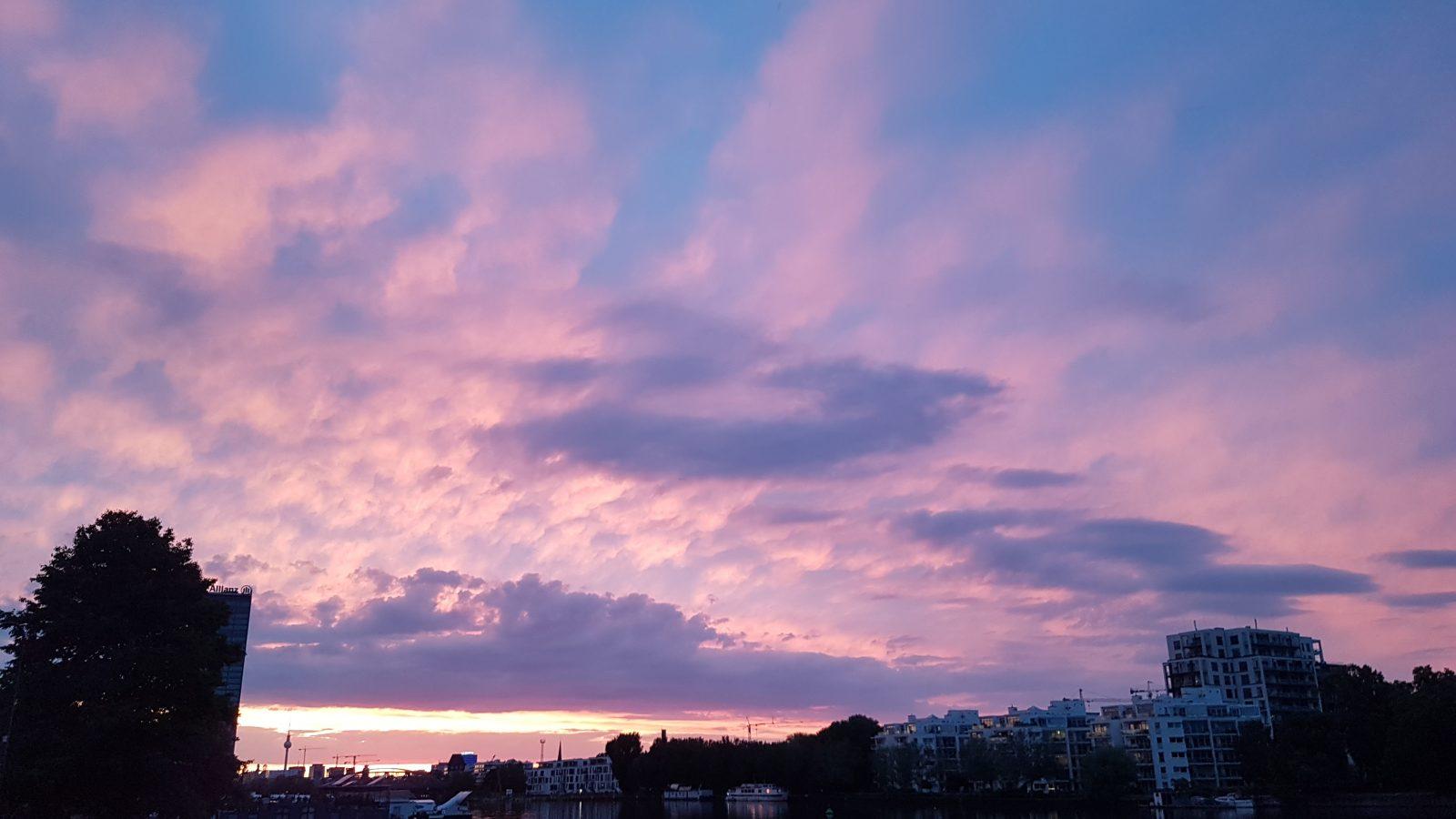 Das Bild zeigt einen rosa Abendhimmel über einem Gewässer.