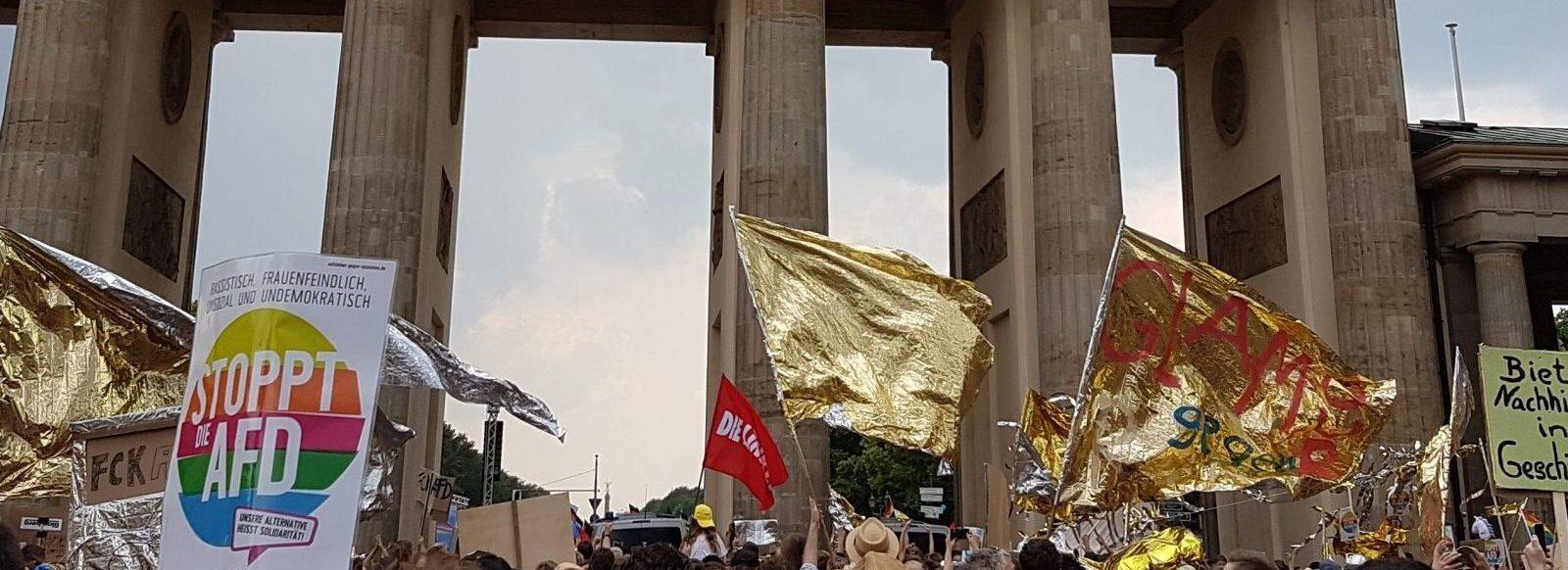 """Das Bild zeigt das Branenburgertor. Davor ist eine Demonstration. Leute halten Schilder und goldene Folien in die Luft. Auf einem Plakat steht """"stoppt Afd"""""""