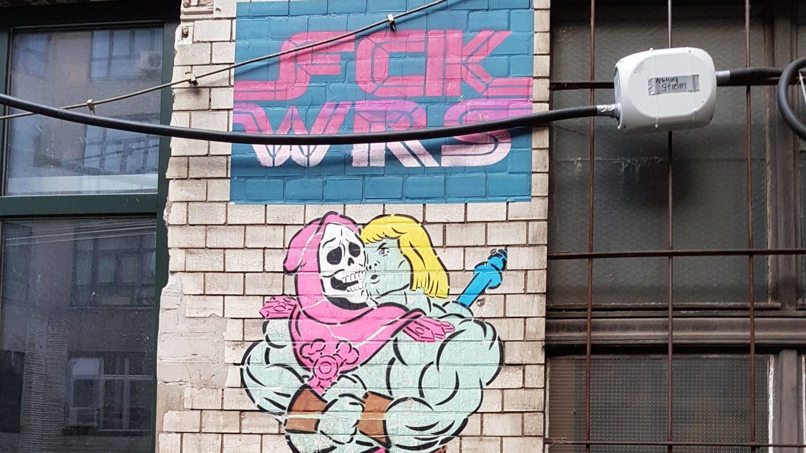 """Das Bild zeigt ein Graphitti. Zwei männlich aussehende Comic Helden küssen sich und darüber steht """"Fuck wars"""""""