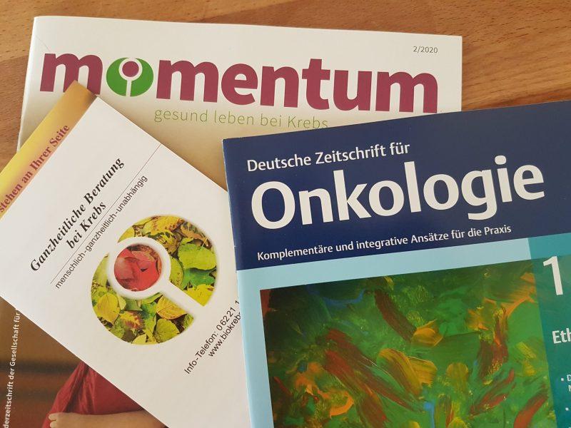 Das Bild zeigt eine Broschüre der biologischen Krebsabwehr und zwei Magazine zu ganzheitlicher Onkologie