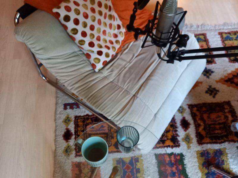 Bild zeigt einen Sessel mit einem Podcast Mikrofon. Daneben ein Beistelltisch mit Kaffeetasse