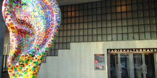 Das Bild zeigt den Eingang zum Radiokulturhaus in Wien. Davor ist eine Skulptur in der Form eines Ohrs. Das Ohr ist aus bunten Steinchen zusammengesetzt.