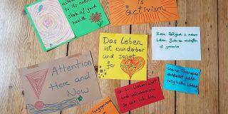 Das Bild zeigt bunte Plakate auf denen positive Affirmationen stehen. Wie zum Beispiel: selfcare is activism, das Leben ist wunderbar und sorgt für mich. Attention: here and now